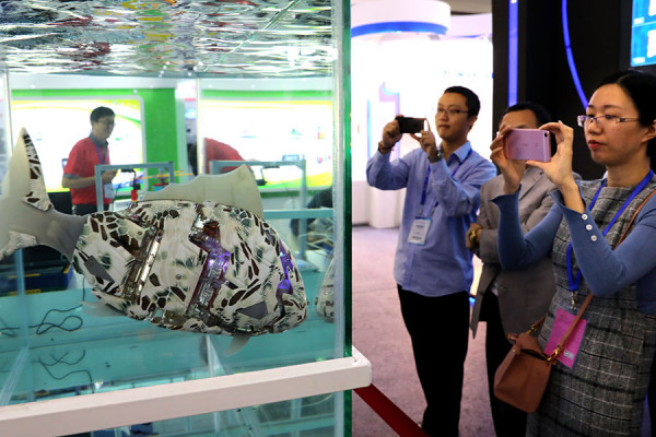 Visitors take photographs of an underwater robot in a tank at the China High-tech Fair 2017 held in Shenzhen, Guangdong province, on Nov 16, 2017. Xuan Hui / Provided to China Daily