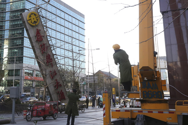 Workers remove a giant sign of a hotel in downtown Beijing last month that is deemed to have violated relevant regulations. (Photo by LIU MANQING/FOR CHINA DAILY)