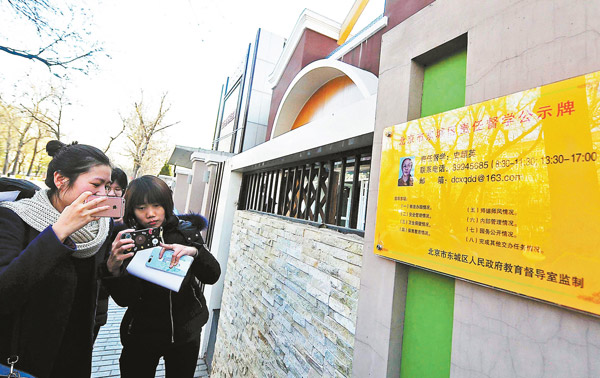 People take photos of the information board of an educational inspector outside a kindergarten in Beijing earlier this month. (Photo by YUAN YI/FOR CHINA DAILY)