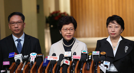 Hong Kong Chief Executive Carrie Lam Cheng Yuet-ngor (center) speaks to the media on Friday with new Secretary for Justice Teresa Cheng Yeuk-wah (right) and Rimsky Yuen Kwokkeung, who is leaving the post. (Photo/China Daily)