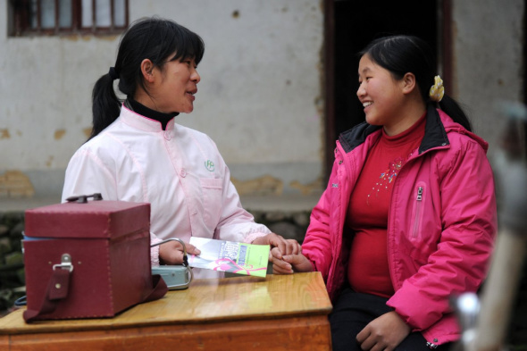 A family planning officer explains a healthcare pamphlet to a pregnant woman in Zhengang, Jiangxi. (Photo/Xinhua)