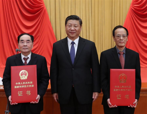 Chinese President Xi Jinping (C) poses for a photo with explosives expert Wang Zeshan (R) and virologist Hou Yunde, winners of China's top science award, at the National Science and Technology Award Conference in Beijing, capital of China, Jan. 8, 2018. (Xinhua/Ju Peng)