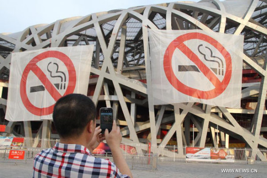 Non-smoking banners are displayed on the iconic Bird's Nest National Stadium in Beijing,June 1, 2015. (Photo/Xinhua)