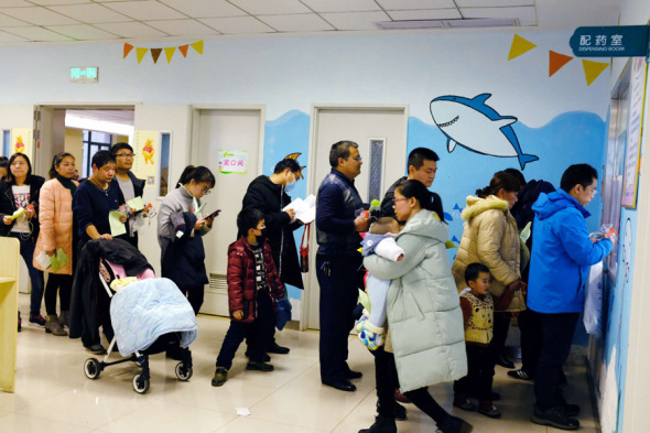 Parents wait in line with their children suffering from flu to get treatment at Wuhan Women and Children Medical Care Center in Hubei province on Sunday. (Photo by Jin Siliu/For China Daily)