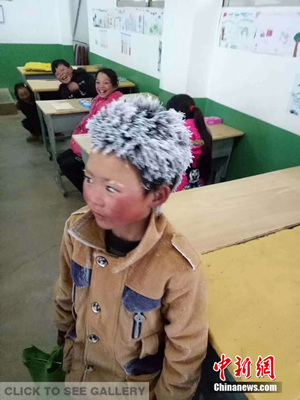 A third-grade boy at Zhuanshanbao Elementary School in Xinjie Town, Zhaotong City of Yunnan Province arrives at a classroom with his hair and eyebrows fully covered with frost. (Photo provided to China News Service)