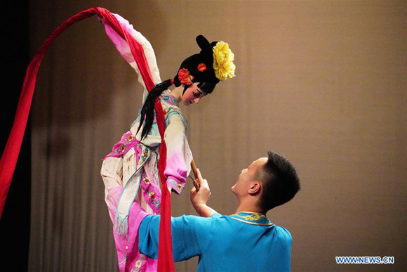 An artist performs puppet dance during a Chinese cultural performance at the Royal Cultural Center in Amman, Jordan, on Feb. 5, 2018. A series of Chinese cultural shows on Monday kicked off in Amman to celebrate the upcoming Chinese New Year which falls next week. (Xinhua/Lin Xiaowei)  AMMAN, Feb. 5 (Xinhua) -- A series of Chinese cultural shows on Monday kicked off in Jordanian capital Amman to celebrate the upcoming Chinese New Year which falls next week.  The cultural performance was held by the Chinese embassy in Amman in cooperation with Jordan's Ministry of Culture and the Greater Amman Municipality at the Royal Cultural Center.  The shows include folk music, traditional dance, acrobatics, puppet dance and mysterious Sichuan opera