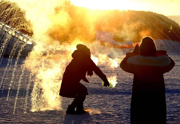"By splashing water into the air, a tourist has created a ""snow firework"" at dusk as the temperatures drop deeper. (Xinhua)"