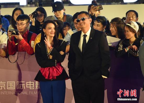 2018年4月15日,第八届北京国际电影节(BJIFF)在北京举行开幕式之前,导演王家卫和女演员舒淇在红地毯上出现。(照片:中国新闻社/翟路)