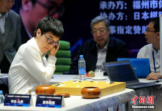 Ke Jie (L) is playing Go with Golaxy, a Chinese-developed AI program. (Photo: China News Service/Wang Dongming)