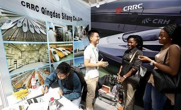 An employee from China Railway Rolling Stock Corp chats with two women at a job fair for international students at Peking University. (Zhu Xingxin/China Daily)