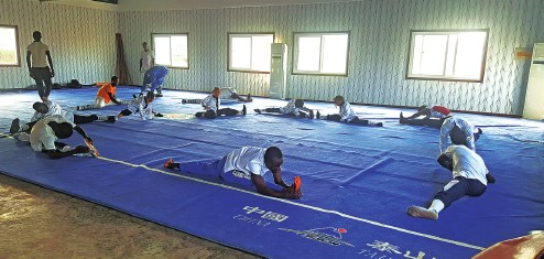 Students of the Chinese Wushu School in Monrovia, Liberia, stretch during daily practice. (Photo provided to China Daily)