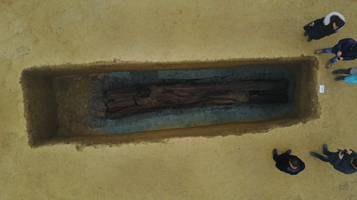 Archeologists gather around a wooden coffin discovered at the M154 site in Sichuan Province. (Photo/Courtesy of Wang Tianyou)