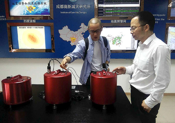 Wang Tun (right), head of the Chengdu-based Institute of Care-Life, demonstrates a seismic monitoring station.  (Photo: China Daily/Huang Zhiling)