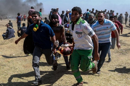 Palestinian medics and protesters carry an injured man during clashes with Israeli troops near the Gaza-Israel border, east of Gaza City, on May 14, 2018. (Xinhua/Wissam Nassar)