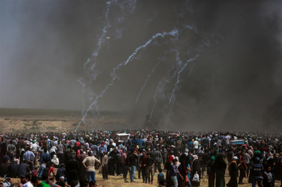 Palestinian protesters clash with Israeli troops near the Gaza-Israel border, east of Gaza City, on May 14, 2018. More than 40 Palestinians, including children, were killed Monday in a day of violent clashes with Israeli forces on Israel's southern border with Gaza, according to the Gaza health ministry. (Xinhua)