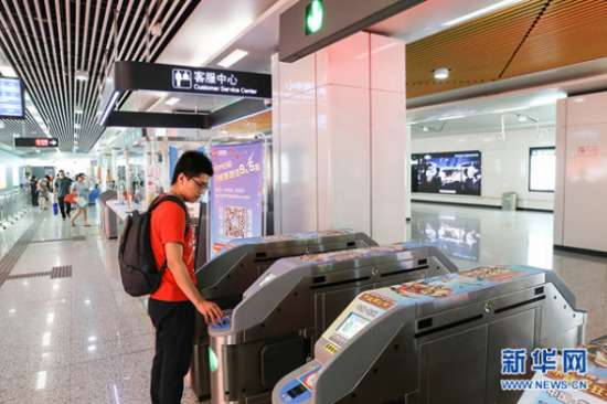 A passenger swipes his smart phone at a subway station in Beijing.