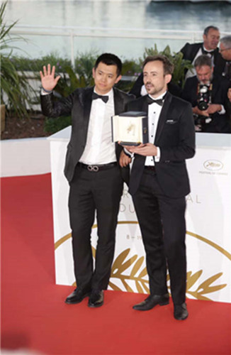 Wei Shujun takes a photo with Australian director Charles Williams, who won the Short Film Palme d'Or for his movie, All These Creatures. (Photo provided to China Daily)