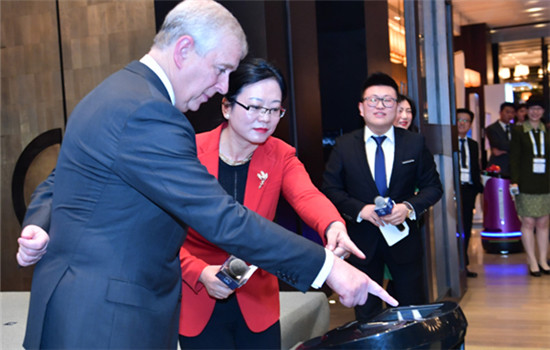 Prince Andrew pushes a button to receive a gift from Run the robot at the opening ceremony of a venture capital platform in Beijing on Oct 26.