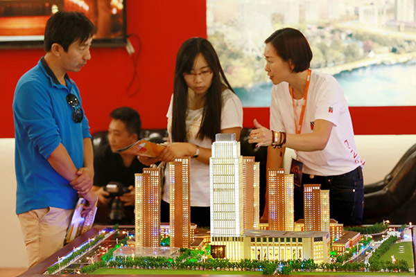 Prospective homebuyers enquire about an upcoming residential property at a Beijing real estate fair. Recent measures against speculative property investments are said to be pushing demand from top-tier cities to small cities. (Photo provided to China Daily)