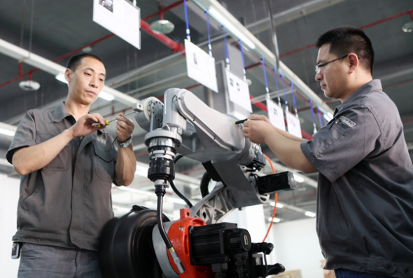Two technicians adjust a robot at a high-tech enterprise in Chongqing. (Photo: Chen Shichuang/For China Daily)