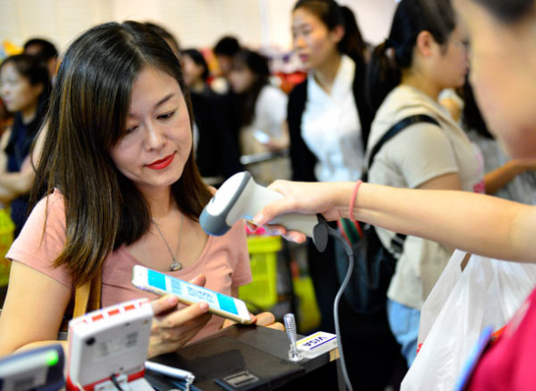 A woman pays via Alipay at a shop in Singapore.