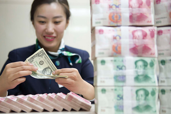 A clerk counts cash at a bank in Taiyuan, capital of Shanxi province. (Photo/China News Service)