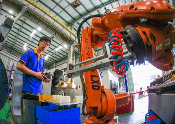 A worker assembles a robotic arm at a factory in Foshan, Guangdong province. (Provided to China Daily)