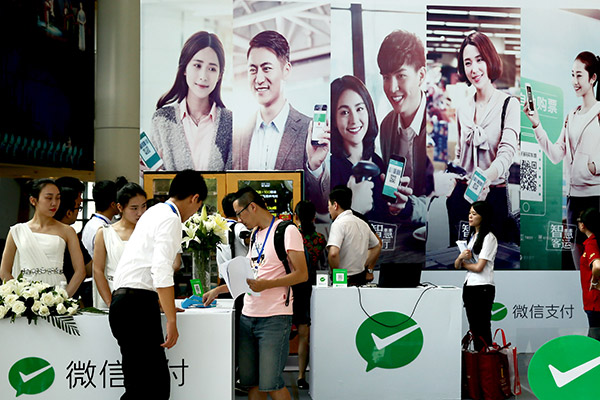 Consumers use WeChat Pay at an exibition in Fuzhou, Fujian province. (Photo/for China Daily)