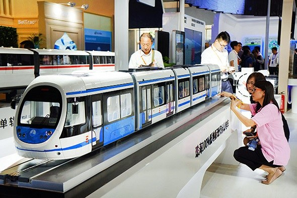 Visitors look at the latest models of urban rail trains shown at the International Urban Rail Exhibition in Beijing.(Photo by Guo Junfeng/Xinhua)