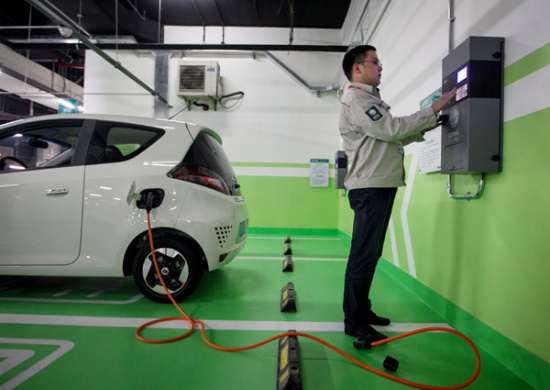 A technician from State Grid Shanghai Municipal Electric Power Co inspects the charging piles, or power ports, in a parking lot before they are put into operation. (Photo/Xinhua)