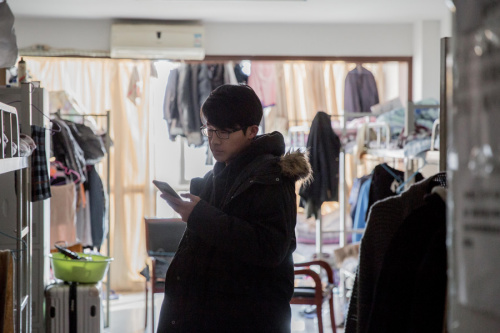 A tenant in a Beijing apartment checks his smartphone for leads to cheaper accommodation. (Photo provided to China Daily)