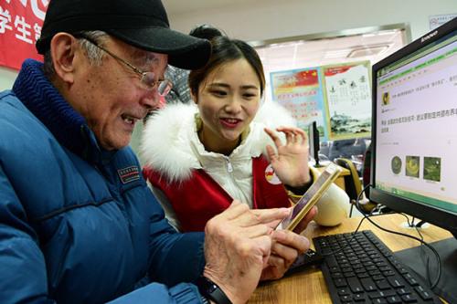 A volunteer helps a senior citizen surf the internet in Zhenjiang, Jiangsu Province. (Photo by Shi Yucheng/for China Daily)