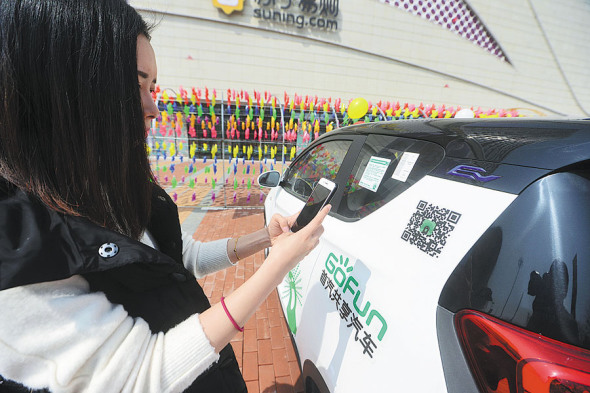 A Hangzhou resident scans the QR code on a shared car. (Photo/China Daily)