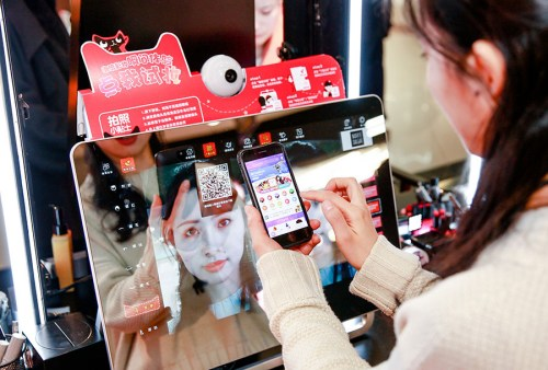 A customer uses a mobile app to select cosmetics for trial at a Tmall pop-up store in a shopping mall in Shanghai. (Photo provided to China Daily)
