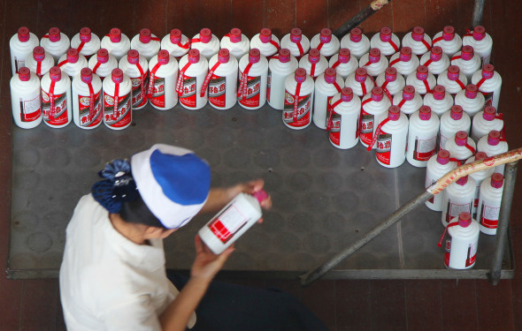An employee works on a production line of Moutai, a brand name Chinese liquor distilled in Southwest China's Guizhou Province. (Photo by Da Shan/For China Daily)