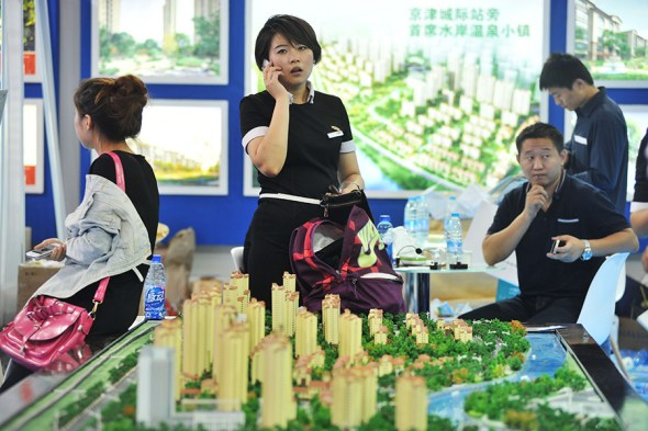 Prospective homebuyers look at a residential property project model at a real estate exhibition in Beijing. (Photo provided to China Daily)