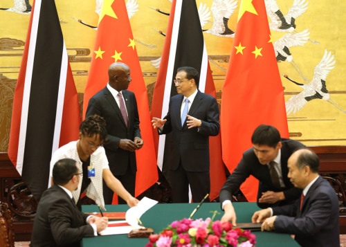 Premier Li Keqiang and visiting Prime Minister Keith Rowley of Trinidad and Tobago witness the signing of documents on cooperative initiatives in the Great Hall of the People in Beijing on Tuesday. (FENG YONGBIN/CHINA DAILY)
