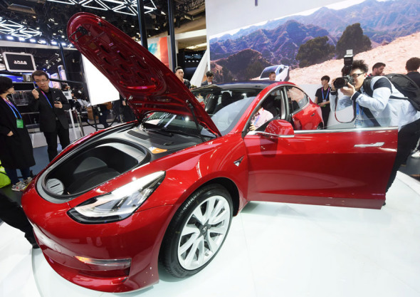 Visitors take photographs of a Tesla electric car at a recent automobile exhibition held in Beijing. (Photo by Long Wei/For China Daily)