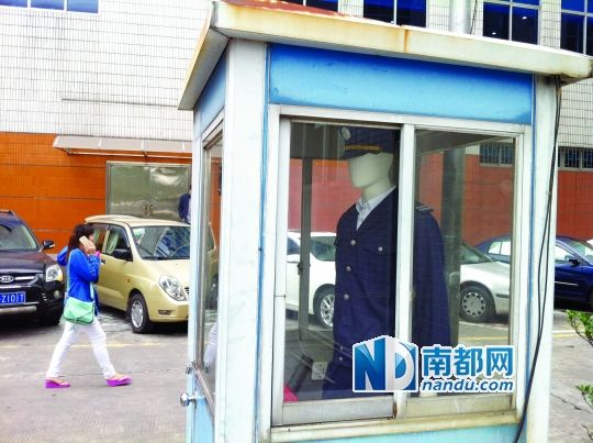 A dummy wearing a security uniform positioned in a sentry booth.