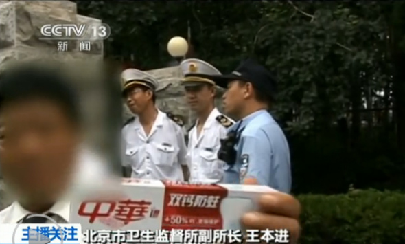A staff member of a conference center attached to the China National Tobacco Corporation (CNTC), a state-owned manufacturer of tobacco products, shows a box of toothpaste when anti-smoking law enforcers inspect the center. (Photo/Screenshot from CCTV)