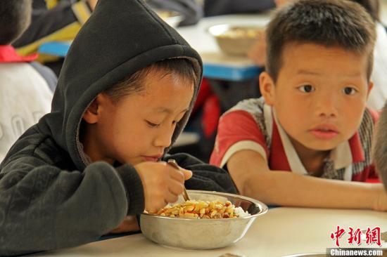 Children have their meal provided by government-funded program. (File photo/Chinanews.com)