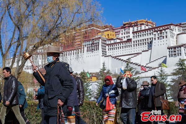 Believers make religious circumambulation around the Potala Palace. (Photo: China News Service/He Penglei)