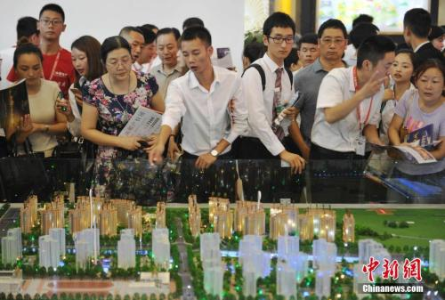 Would-be home buyers visit a real estate sales center. (Photo/China News Service)