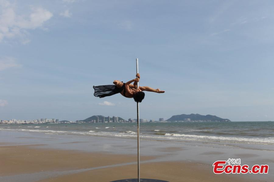 Fang Yi, member of China\'s national pole dancing team shows strength and beauty on a beach in China on Monday, September 15, 2014. China will host the 2015 World Pole Dance Championships in next April. [Photo/ Osports Photo Agency]
