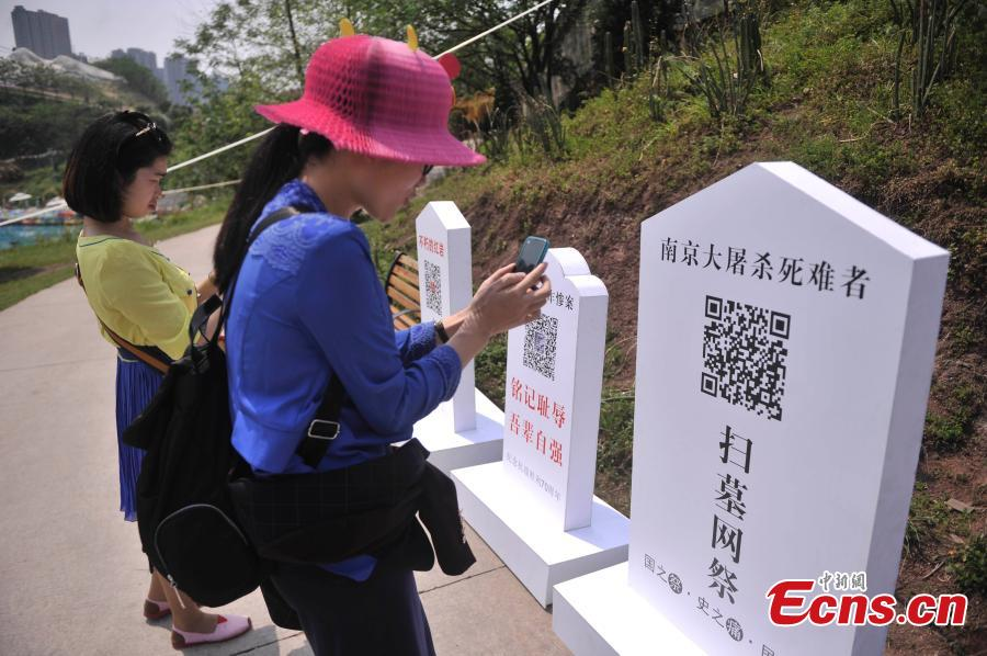 Visitors scan QR codes to commemorate victims of the Nanjing Massacre and Bombing of Chongqing, both committed by Japanese troops in China during World War II, at the theme park Foreigner Street in Southwest China's Chongqing municipality, March 31, 2015. Visitors can take part in an online memorial, by lighting candles, presenting flowers, ringing bells and planting trees. (Photo: China News Service/Chen Chao)