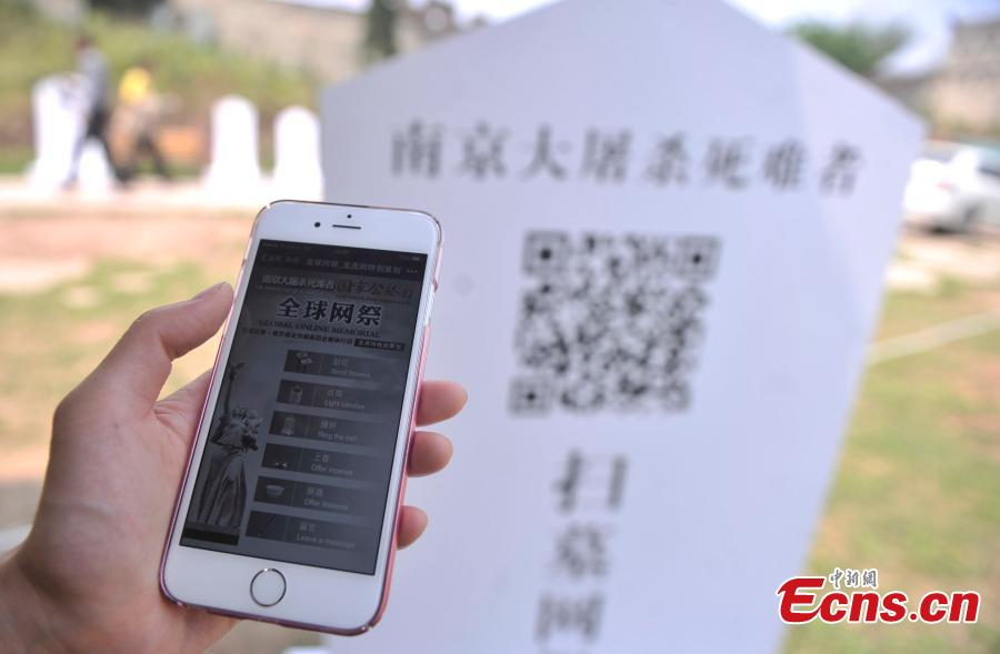 A visitor scans a QR code to commemorate victims of the Nanjing Massacre and Bombing of Chongqing, both committed by Japanese troops in China during World War II, at the theme park Foreigner Street in Southwest China's Chongqing municipality, March 31, 2015. Visitors can take part in an online memorial, by lighting candles, presenting flowers, ringing bells and planting trees. (Photo: China News Service/Chen Chao)