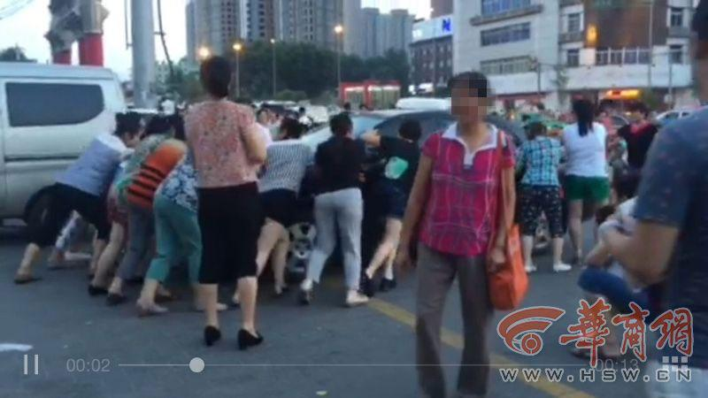More than ten middle-aged women are seen pushing a car parked on the road in Xi\'an, in northwestern China, on 22nd July, 2015. Three cars were reportedly moved successively. The women turned out to be enthusiasts of the evening line dance, known in China as \