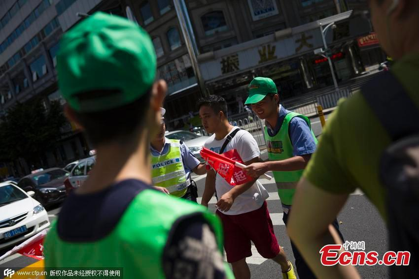 26aaf2c9be6 Traffic rule breakers wear green hats and vests at an intersection in  Shenzhen