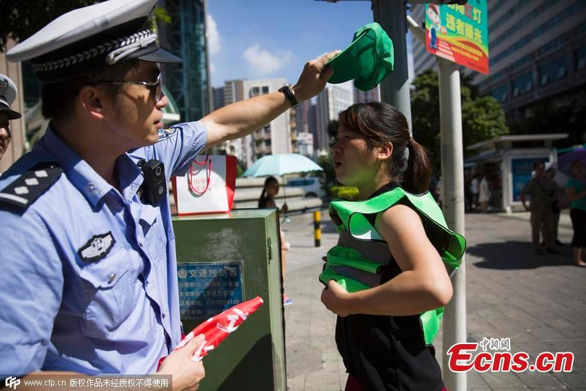 196cdacda98 A policeman puts a green hat on the head of a woman who ran a red