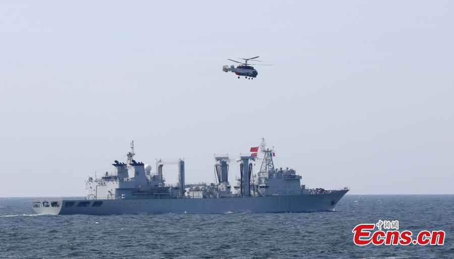 A helicopter flies past Chinese Navy destroyer Hefei during a drill with Russia in the Baltic Sea, July 25, 2017. Chinese and Russian warships went into formations to protect against air attack during the drill. (Photo: China News Service/Wang Xiujun)